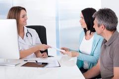 Doktor som ger kortet till patienten Arkivbild