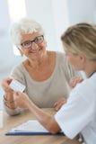 Doktor som ger läkarbehandlingen till den höga kvinnan Arkivbilder