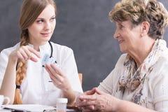 Doktor som ger mediciner till patienten Fotografering för Bildbyråer
