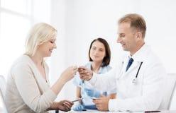 Doktor som ger minnestavlor till patienten i sjukhus arkivbild
