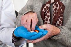Doktor som ger preventivpillerar till den äldre kvinnan fotografering för bildbyråer