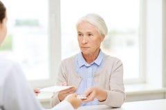 Doktor som ger receptet och drogen till kvinnan Arkivfoto