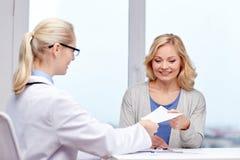 Doktor som ger receptet till kvinnan på sjukhuset Arkivbild