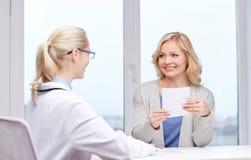 Doktor som ger receptet till kvinnan på sjukhuset Royaltyfri Bild