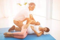 Doktor som ger sjukgymnastik till gravida kvinnan Royaltyfri Foto