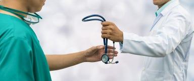 Doktor som ger stetoskopet till kirurgen Referral royaltyfria foton