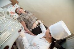 Doktor som gör ultrasoundutredning Arkivfoto