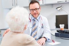 Doktor som i praktiken ser den höga patienten Fotografering för Bildbyråer