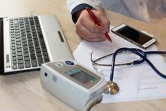 Doktor som i regeringsställning arbetar på tabellen Händer av en doktor som fyller RX Arkivbilder