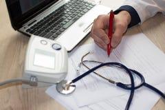 Doktor som i regeringsställning arbetar på tabellen Händer av en doktor som fyller RX Arkivbild