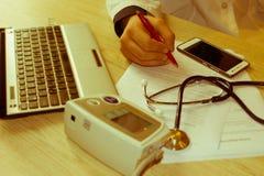 Doktor som i regeringsställning arbetar på tabellen Händer av en doktor som fyller RX Fotografering för Bildbyråer
