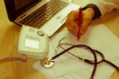 Doktor som i regeringsställning arbetar på tabellen Händer av en doktor som fyller RX Royaltyfri Foto