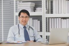 Doktor som i regeringsst?llning sitter, leende och blick p? kameran royaltyfria foton