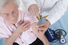 Doktor som injicerar vaccinen till den höga kvinnan royaltyfri fotografi