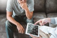 Doktor som konsulterar diagnostiskt undersöka med patienten som framlägger resultat för röntgenstrålefilm på digitalt minnestavla royaltyfria foton