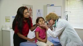 Doktor som kontrollerar öron av det sjuka barnet arkivfilmer