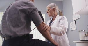 Doktor som kontrollerar blodtryck av den medelåldersa manliga patienten fotografering för bildbyråer