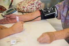 Doktor som kontrollerar gammalt kvinnligt tålmodigt arteriellt blodtryck isolerade fängelsekunder för armomsorg hälsa Arkivbild