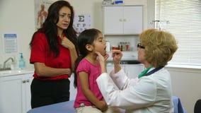 Doktor som kontrollerar halsen av det sjuka barnet arkivfilmer