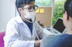 Doktor som kontrollerar hennes puls Manlig läkare som undersöker kvinnlig patie royaltyfri fotografi