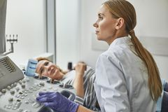 Doktor som kontrollerar kvinnahavandeskap under sonographytillvägagångssätt royaltyfri bild