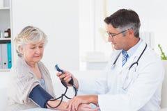 Doktor som kontrollerar kvinnligt patientblodtryck Arkivfoto