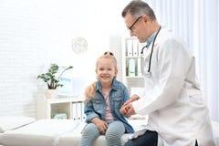Doktor som kontrollerar liten flickas puls med fingrar i sjukhus royaltyfri foto