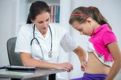 Doktor som kontrollerar magen av den sjuka flickan royaltyfria bilder