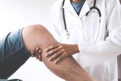 Doktor som kontrollerar patienten med knä för att bestämma orsaken av dåligt royaltyfri foto