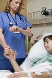 Doktor som kontrollerar patientpuls royaltyfri bild