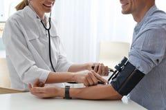 Doktor som kontrollerar patients blodtryck i sjukhuset, closeup arkivbild