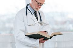 Doktor som l?ser en l?robok royaltyfri fotografi