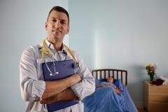 Doktor som ler i offentlig sjukhustålmodiglokal Arkivfoton