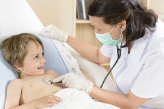 Doktor som lite konsulterar pojken Royaltyfri Bild