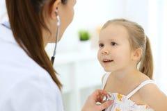 Doktor som lite unders?ker flickan vid stetoskopet Lycklig le barnpatient p? vanlig medicinsk kontroll Medicin och arkivfoto