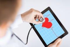 Doktor som lyssnar till hjärtatakten Arkivfoto