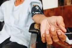 Doktor som mäter blodtryck av den äldre mannen Royaltyfri Foto