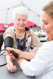 Doktor som mäter blodtryck av den höga patienten Royaltyfri Bild