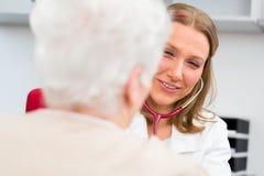 Doktor som mäter blodtryck av den höga patienten Royaltyfria Bilder