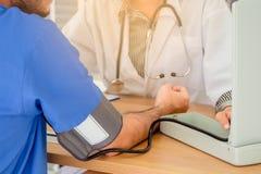 Doktor som mäter blodtryck av den manliga patienten royaltyfri fotografi