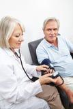 Doktor som mäter blodtryck av pensionären royaltyfria foton