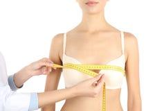 Doktor som mäter format av patients bröst på vit bakgrund, closeup royaltyfri fotografi
