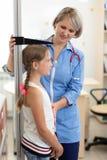 Doktor som mäter höjd för flicka` s royaltyfria foton