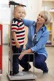 Doktor som mäter höjd för pojke` s royaltyfri bild