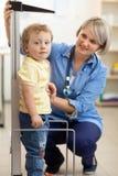 Doktor som mäter höjd för pojke` s arkivfoto