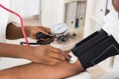 Doktor som mäter patientblodtryck Fotografering för Bildbyråer