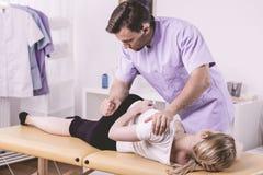Doktor som masserar kvinnan med ryggradproblem arkivbilder