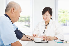 Doktor som mäter blodtryck av den höga mannen Royaltyfri Fotografi