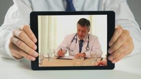 Doktor som rymmer den digitala minnestavlan och har diskussion, i möte stock video