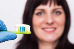 Doktor som rymmer en tandborste med en tandkräm i bakgrunden som ler den caucasian flickan med ett leende, läkarundersökning, när fotografering för bildbyråer
